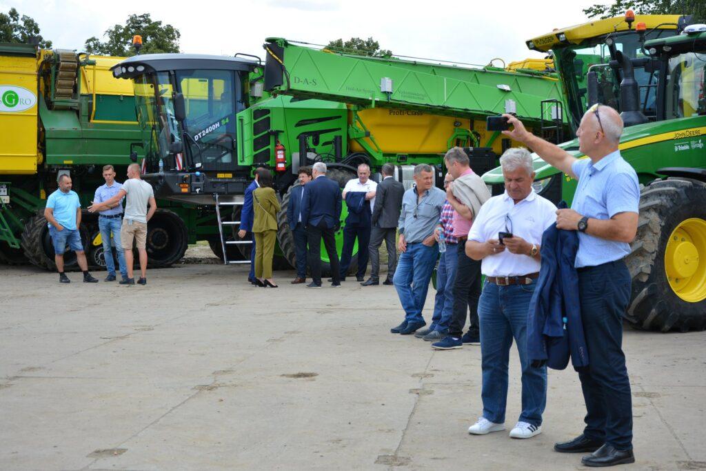 uczestnicy spotkania na tle maszyn rolniczych